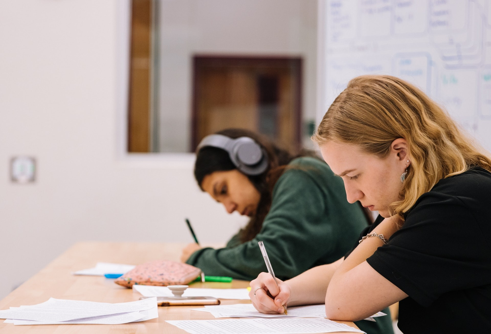 Two students write a test in a classroom.