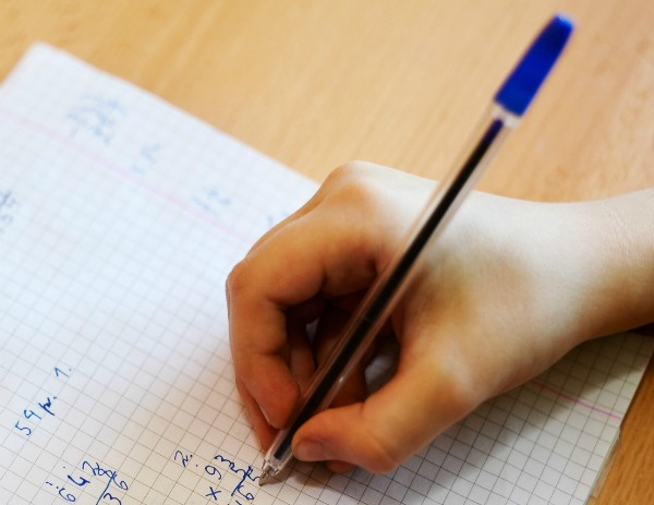 A hand holding a pen is doing calculation on a pice of papper