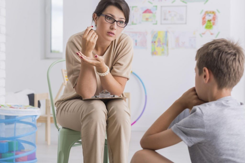 A female teacher sitting on a chair is carefully listening to a student
