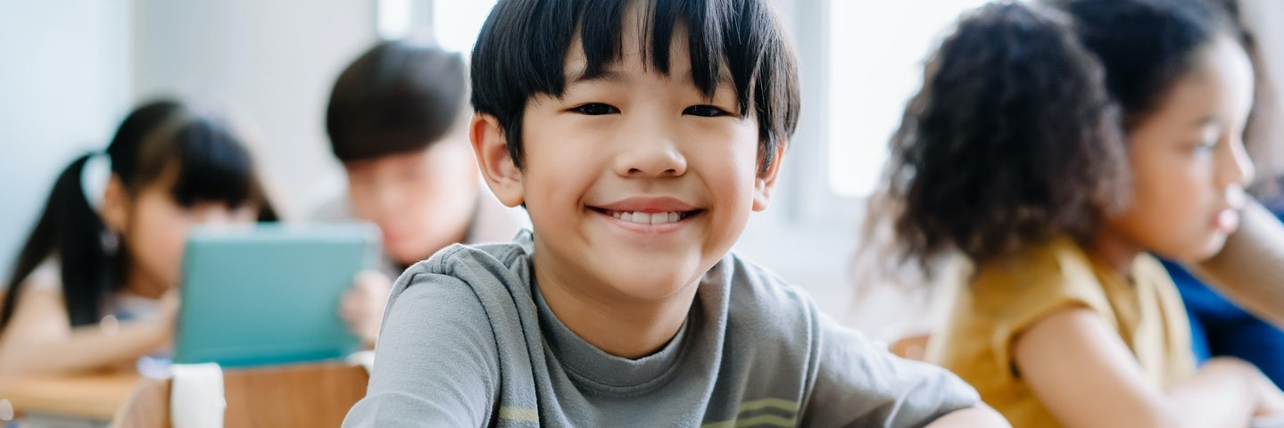 Young boy smiles at the camera while sitting at a desk with a tablet in a classroom.
