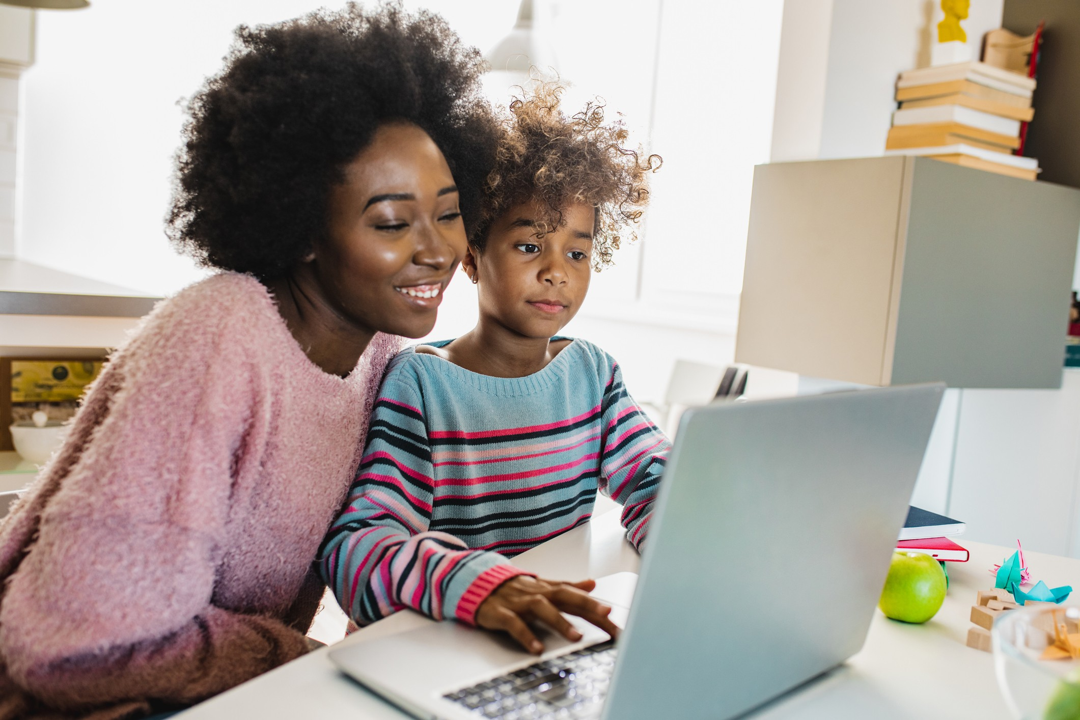A mother and daughter sitting at a laptop together