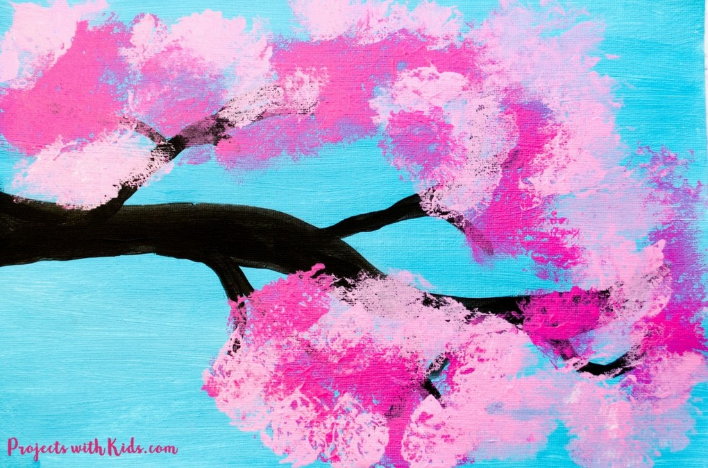 Blue canvas with pink cherry blossom tree painted on it