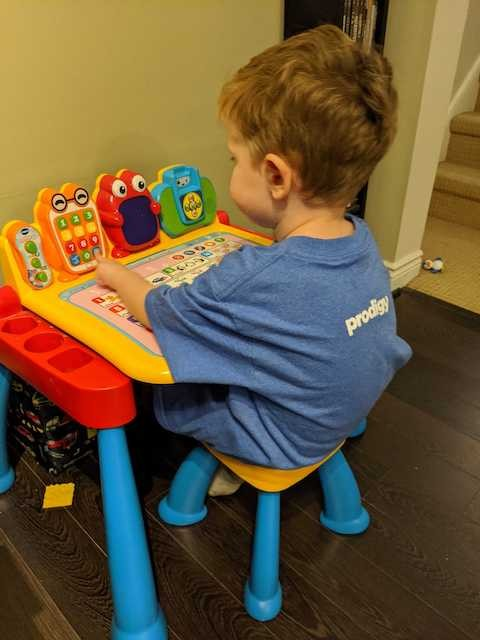 Toddler sitting at play desk