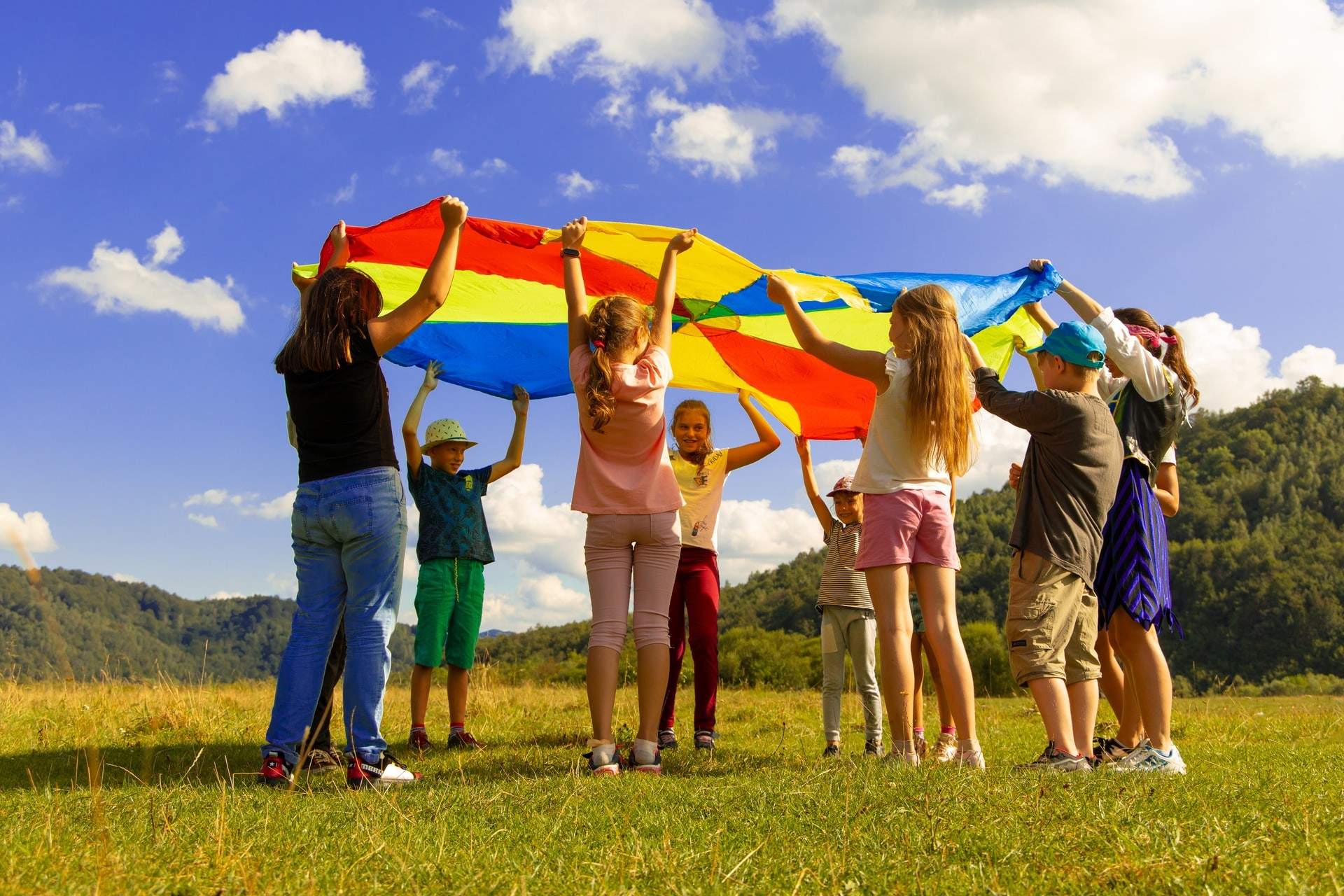 A group of students stands outside holding a colorful circle of fabric as they play active classroom games.