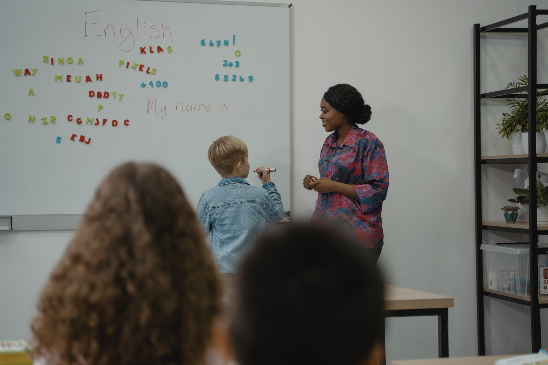 A teacher uses new teaching methods with a student at the whiteboard in english class.