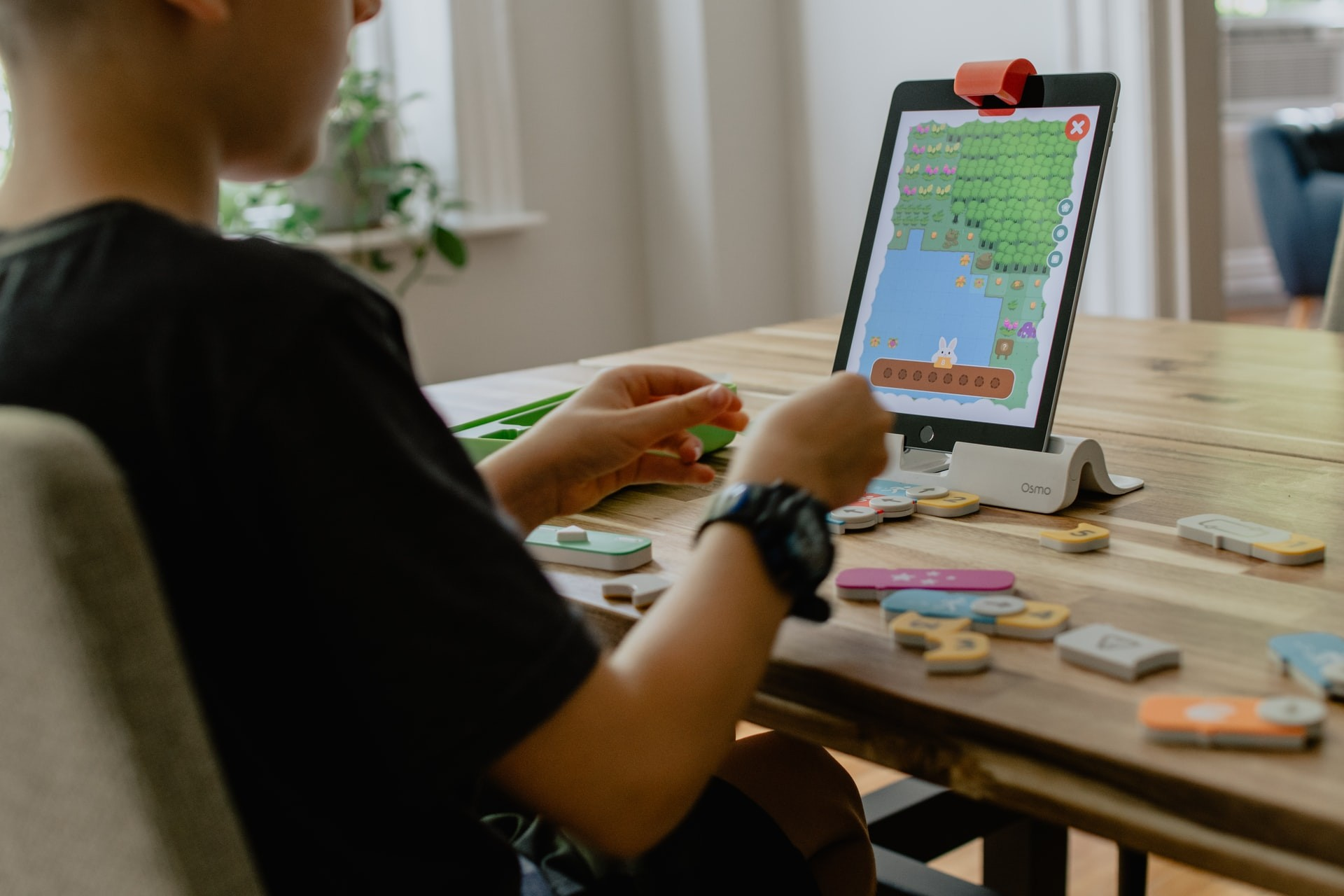 Young boy plays with an online learning game on a tablet while sitting at a kitchen table.