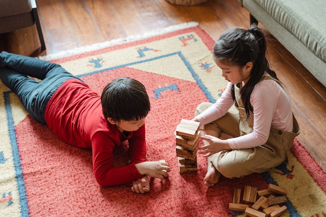 Two siblings laying on a carpet playing Jenga together.
