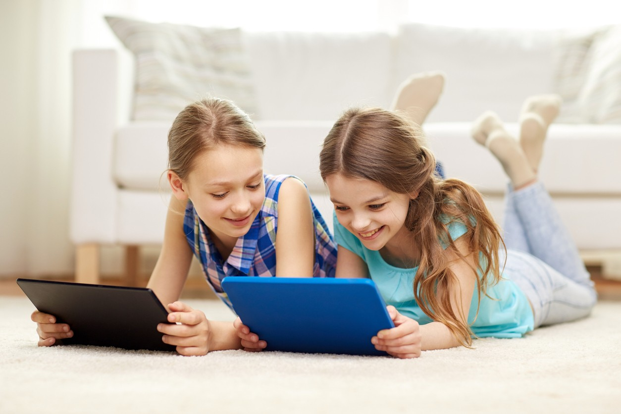 Two girls smiling while playing on tablets.