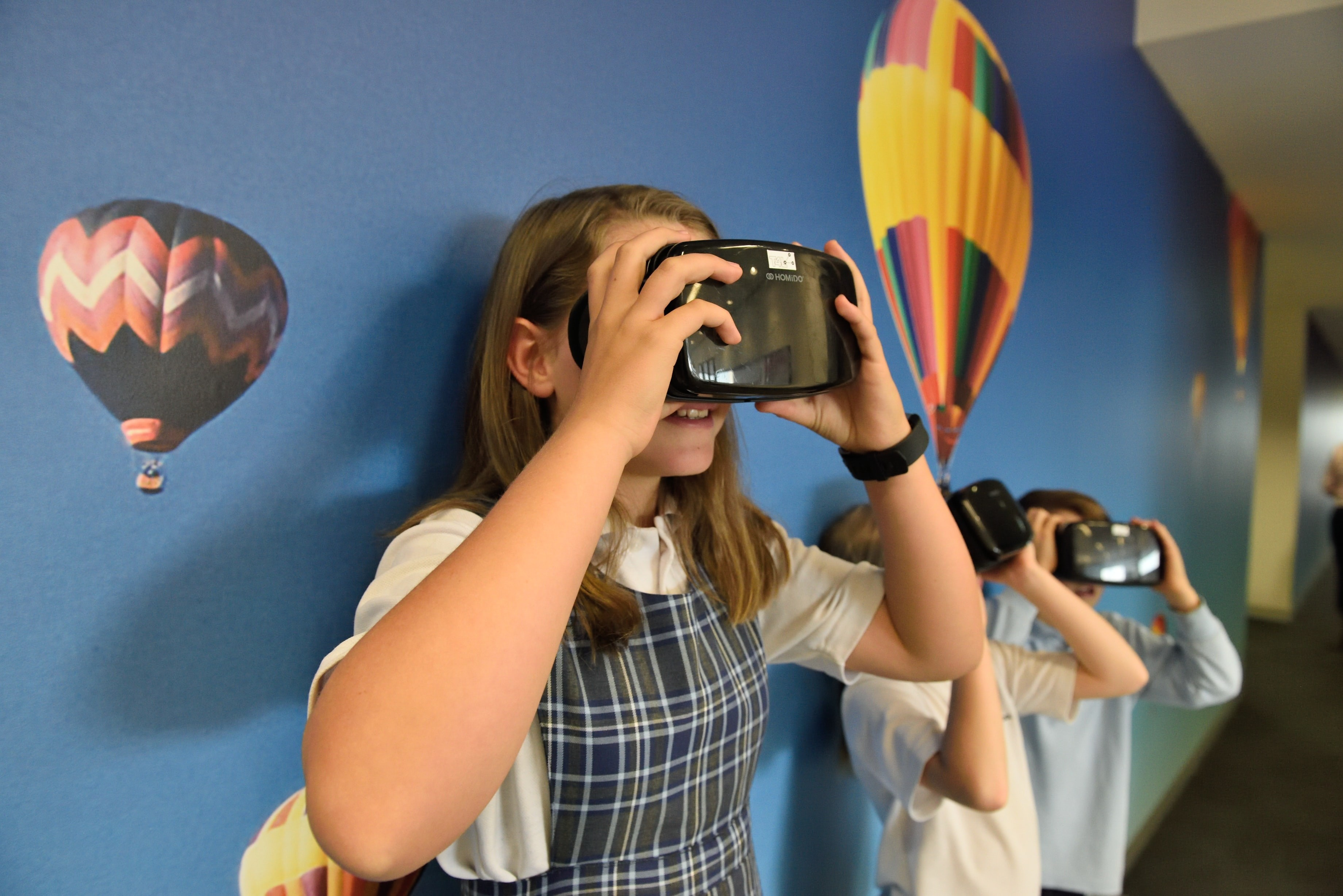 Three students use virtual reality headsets as part of a type of game-based learning activity.