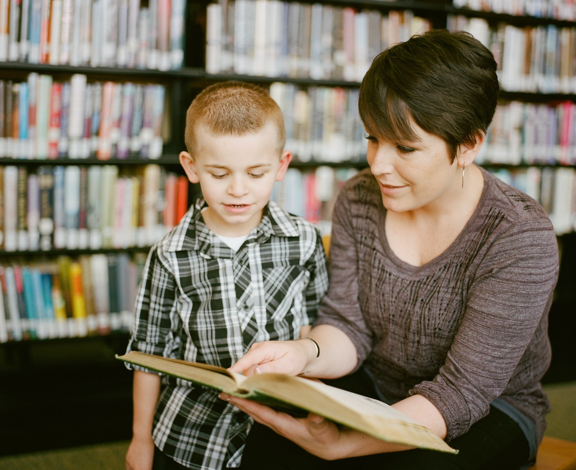 A teacher and student read a book together as part of a personalized learning plan.