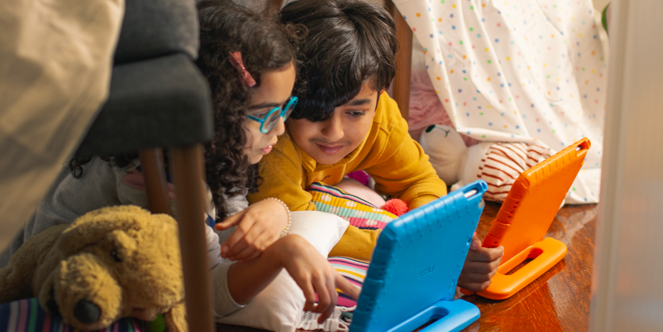 Two children playing on tablet devices.