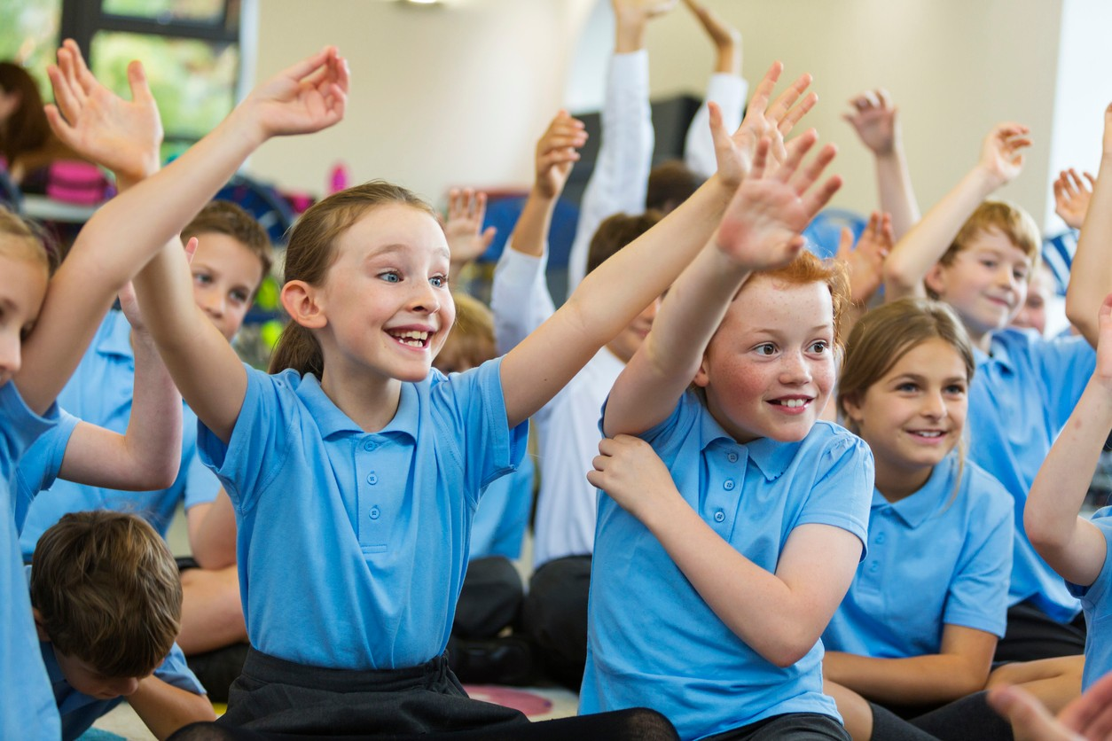 Excited students raise their hands to answer ice breaker questions for kids in their classroom