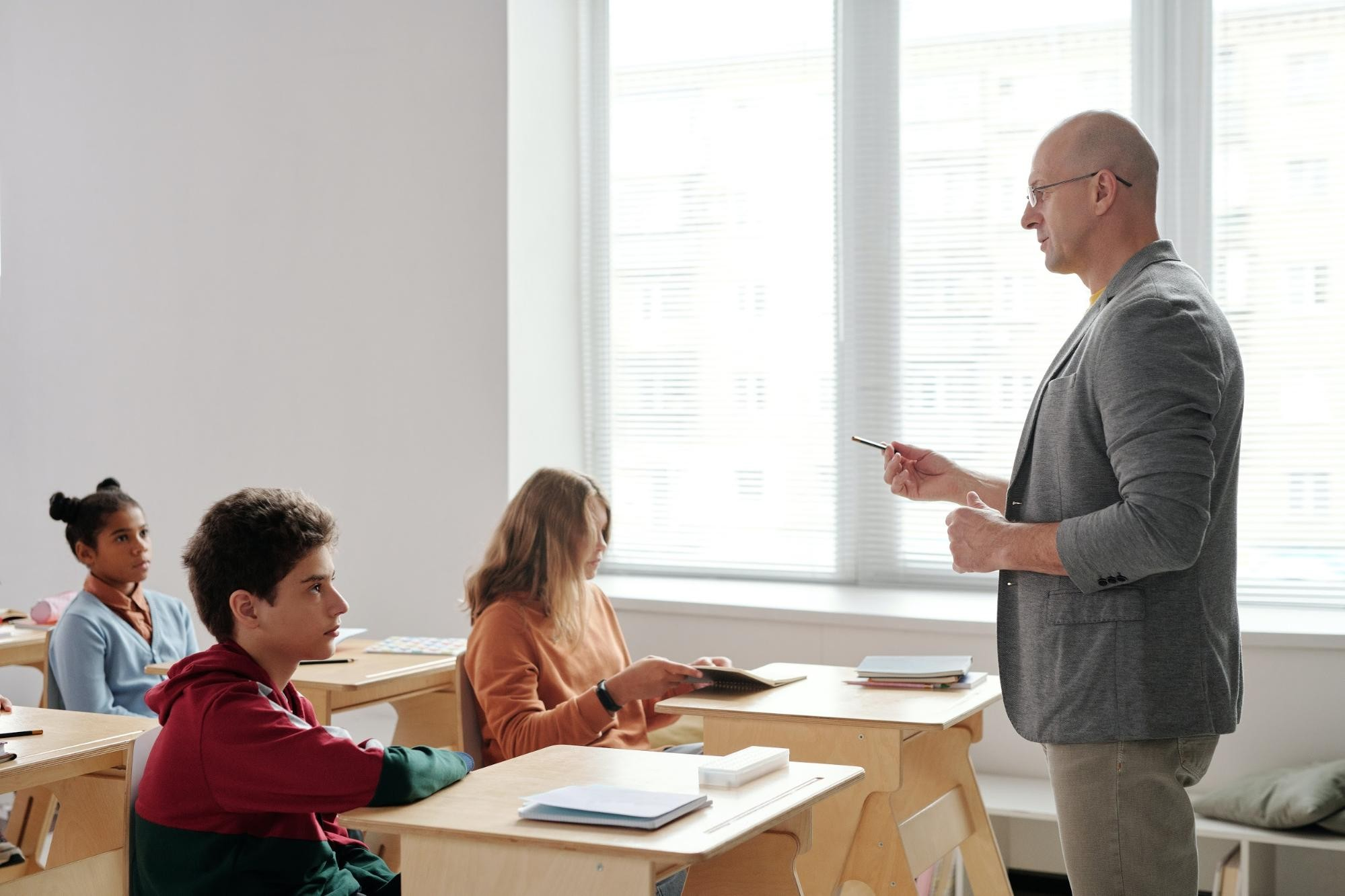 Male teacher in front of students sitting in wooden desks in the classroom.
