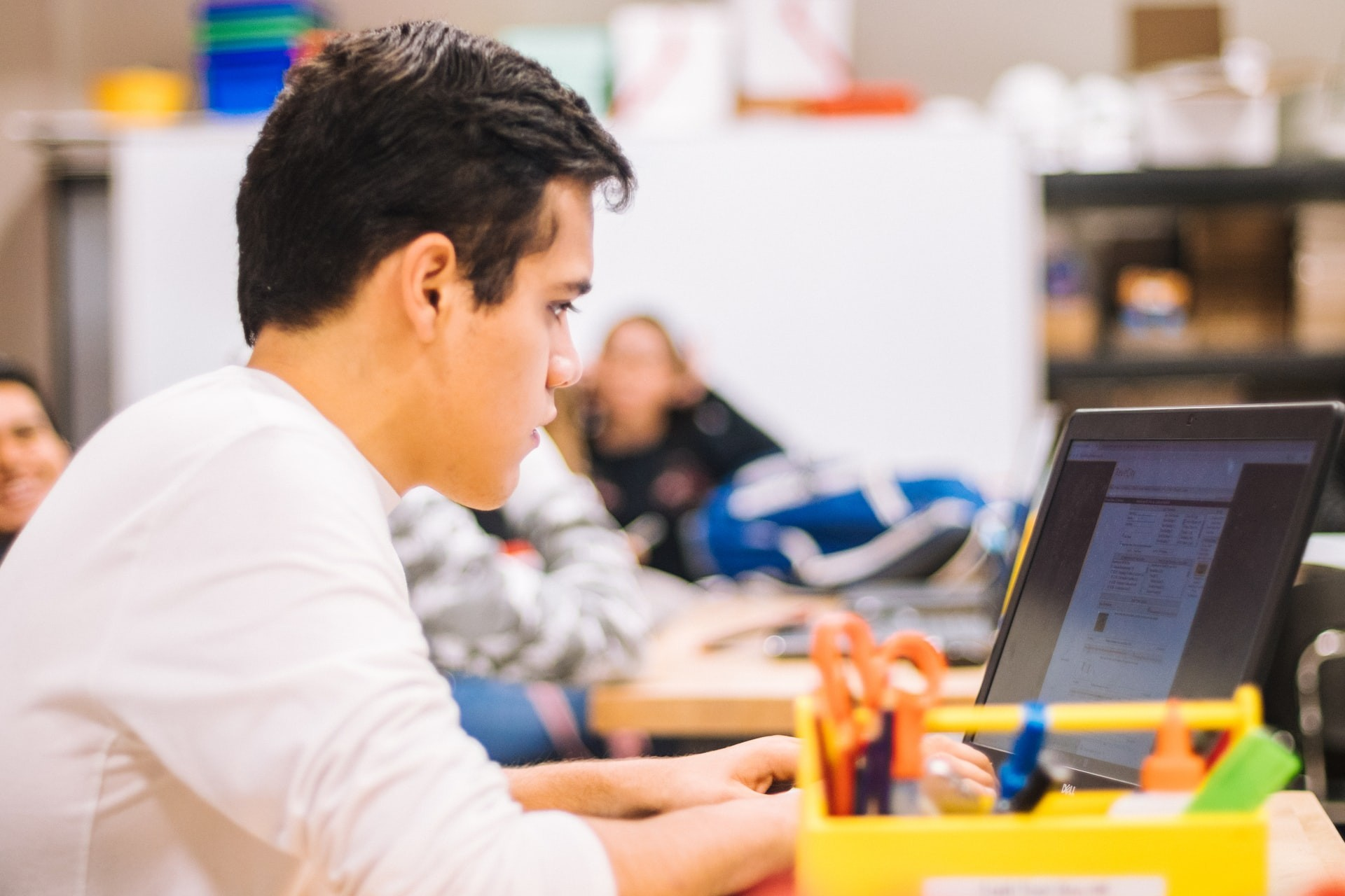 A male student works on a computer in the classroom after returning to in-person learning.