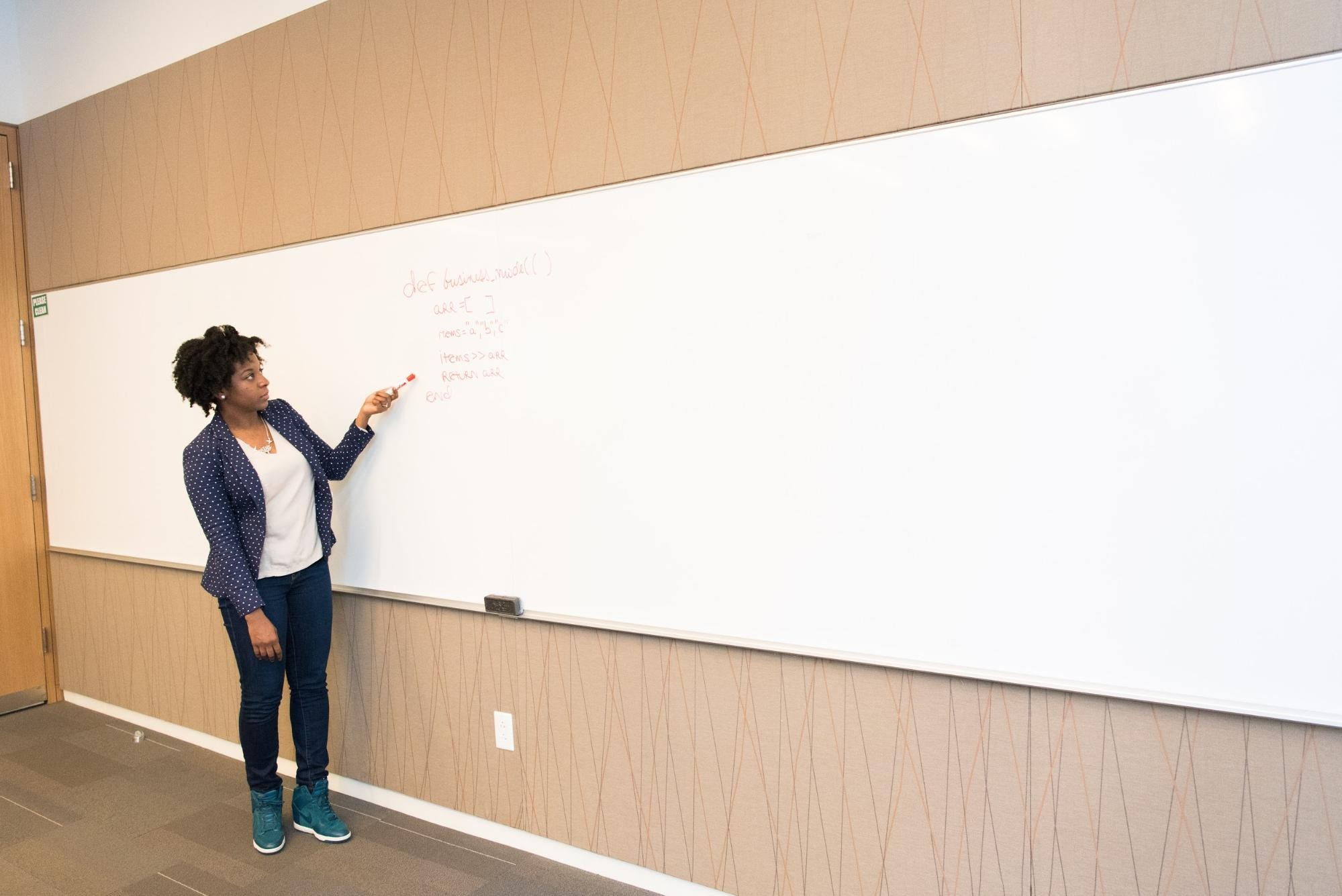 Teacher stands at whiteboard and points with marker at red writing.