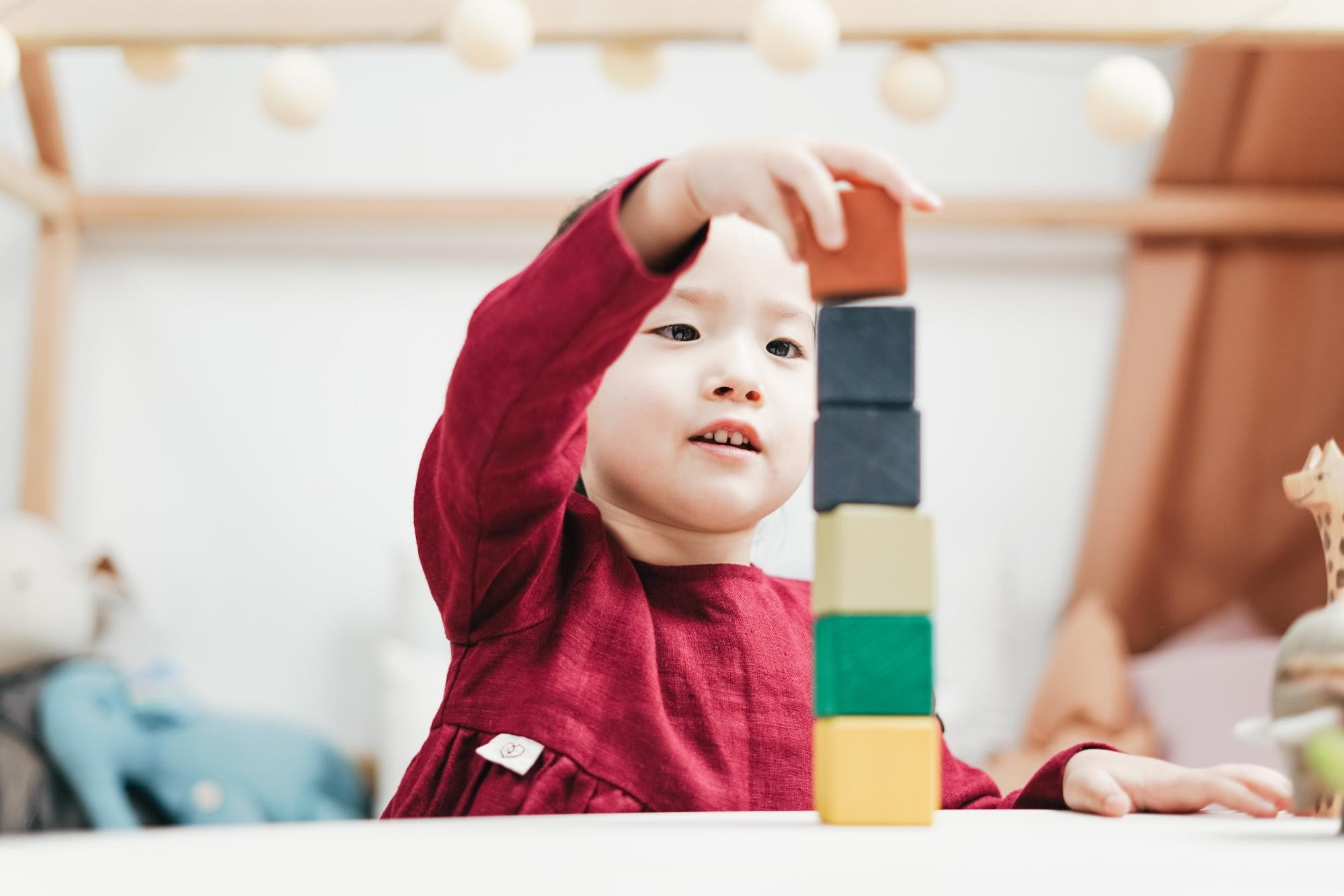 Young child plays with building blocks in the classroom.