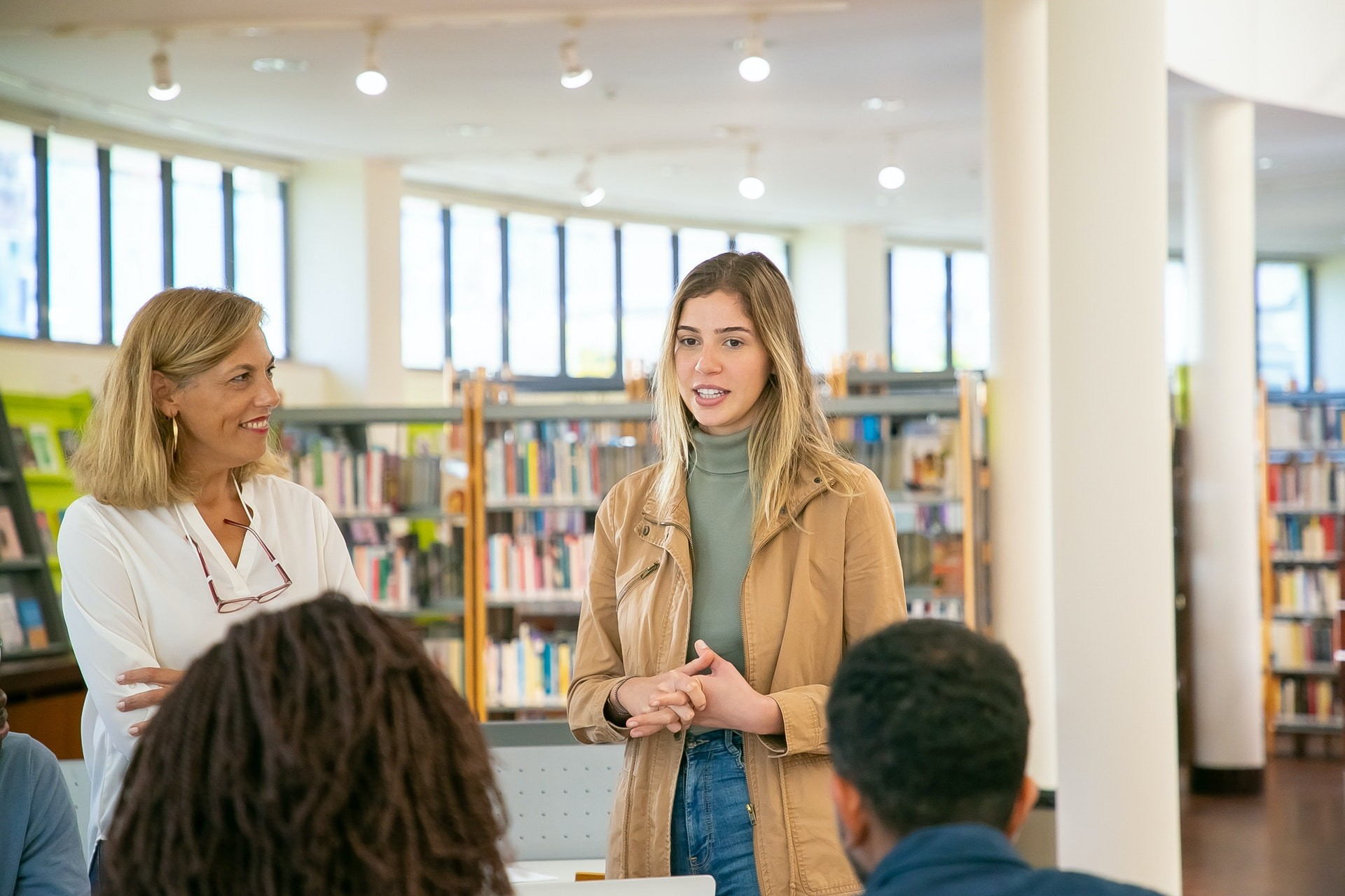 A female student stands in a library and gives a presentation to fellow classmates.