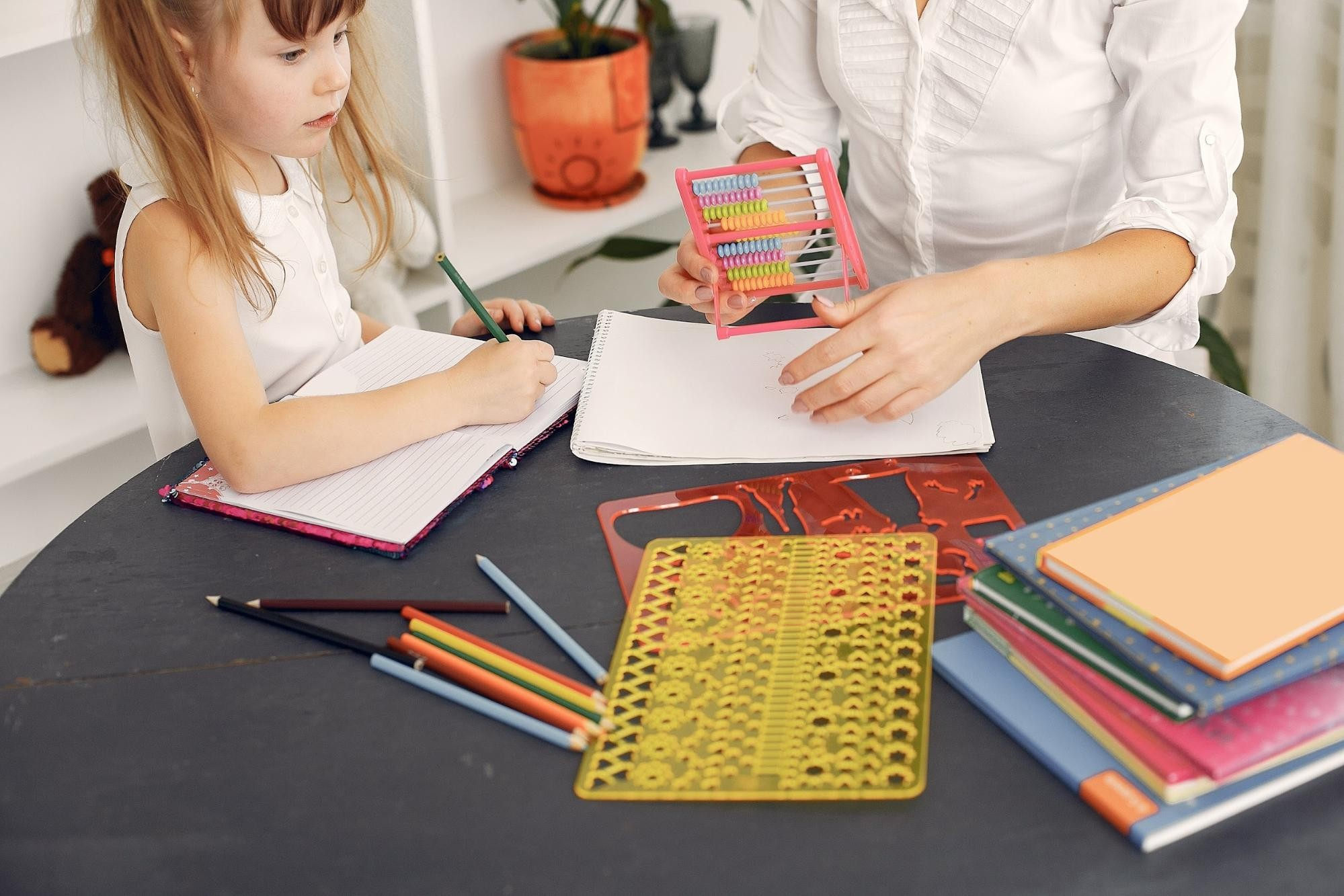 Young girls sits at a table with teachers, writing in a notebook and looking at writing supplies on the table.