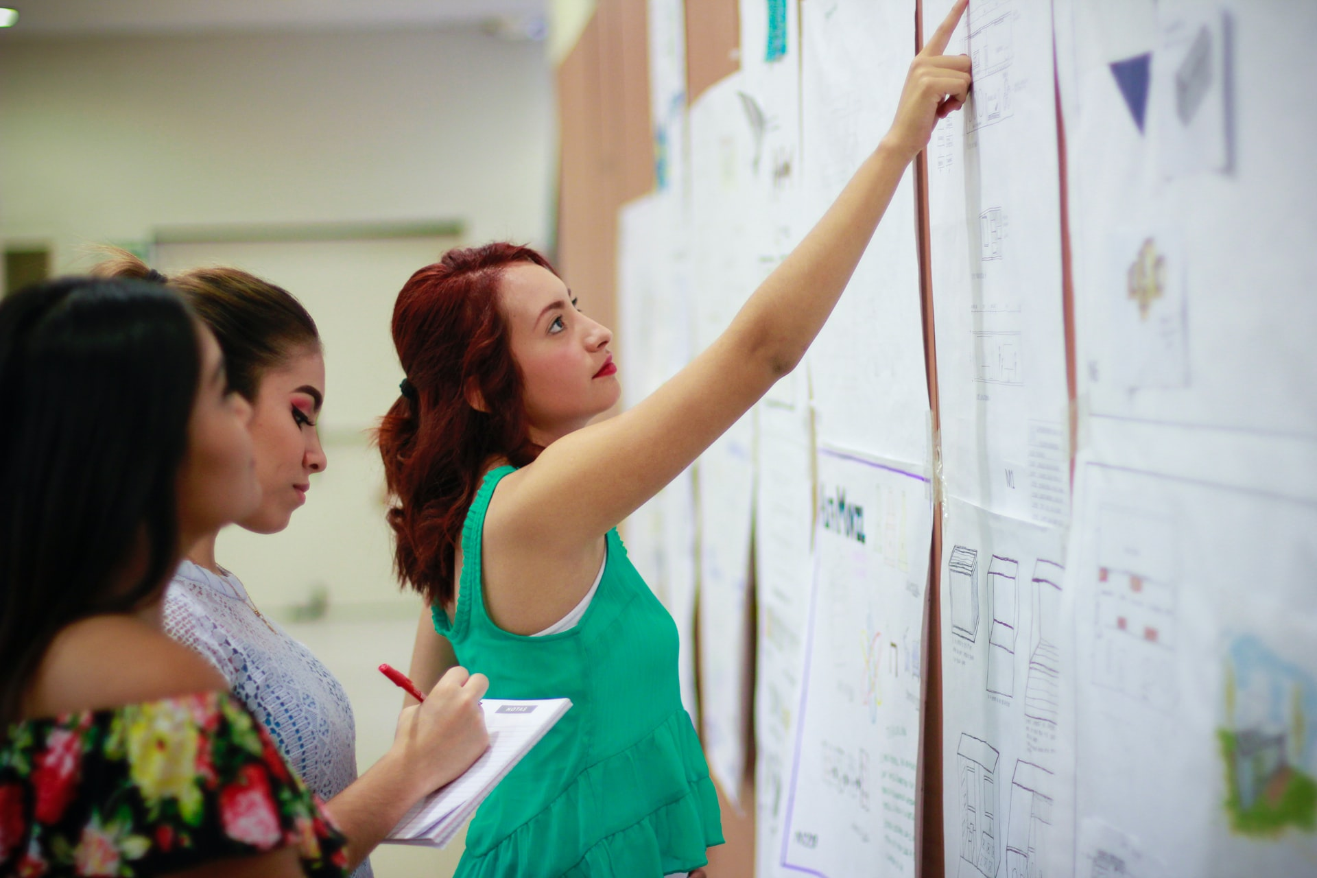 Three women stand in front of a board, one woman with red hair and a green shirt points at a chart while the other two take notes.