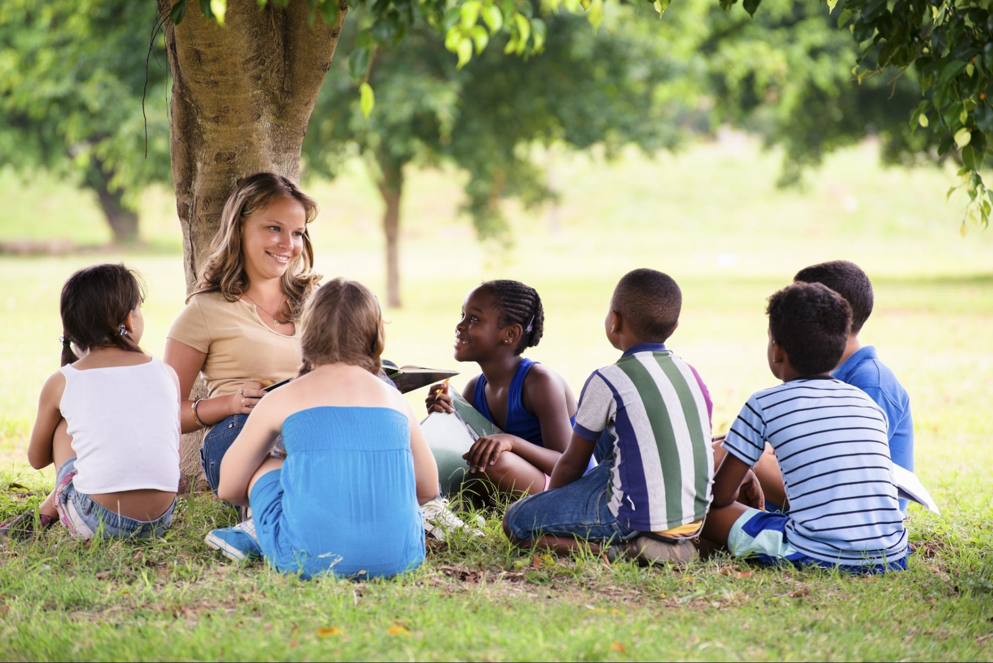 A teacher and a group of students sit outside underneath a tree.