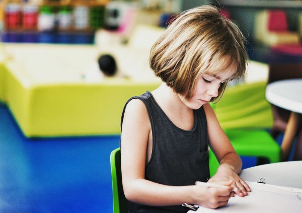 A young girl is sitting and working on her homework