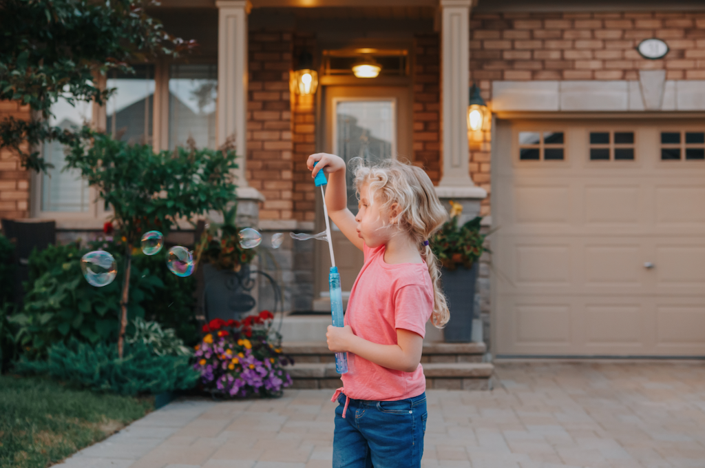 Child blowing bubbles outside during downtime from her homeschooling program