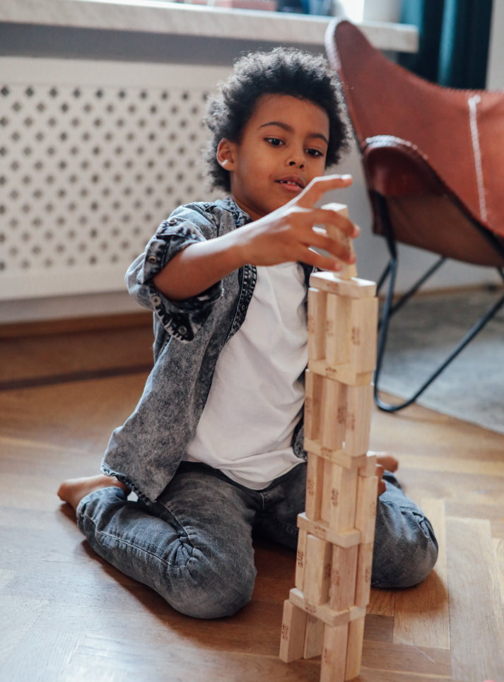 Unschooled child building a tower out of Jenga blocks