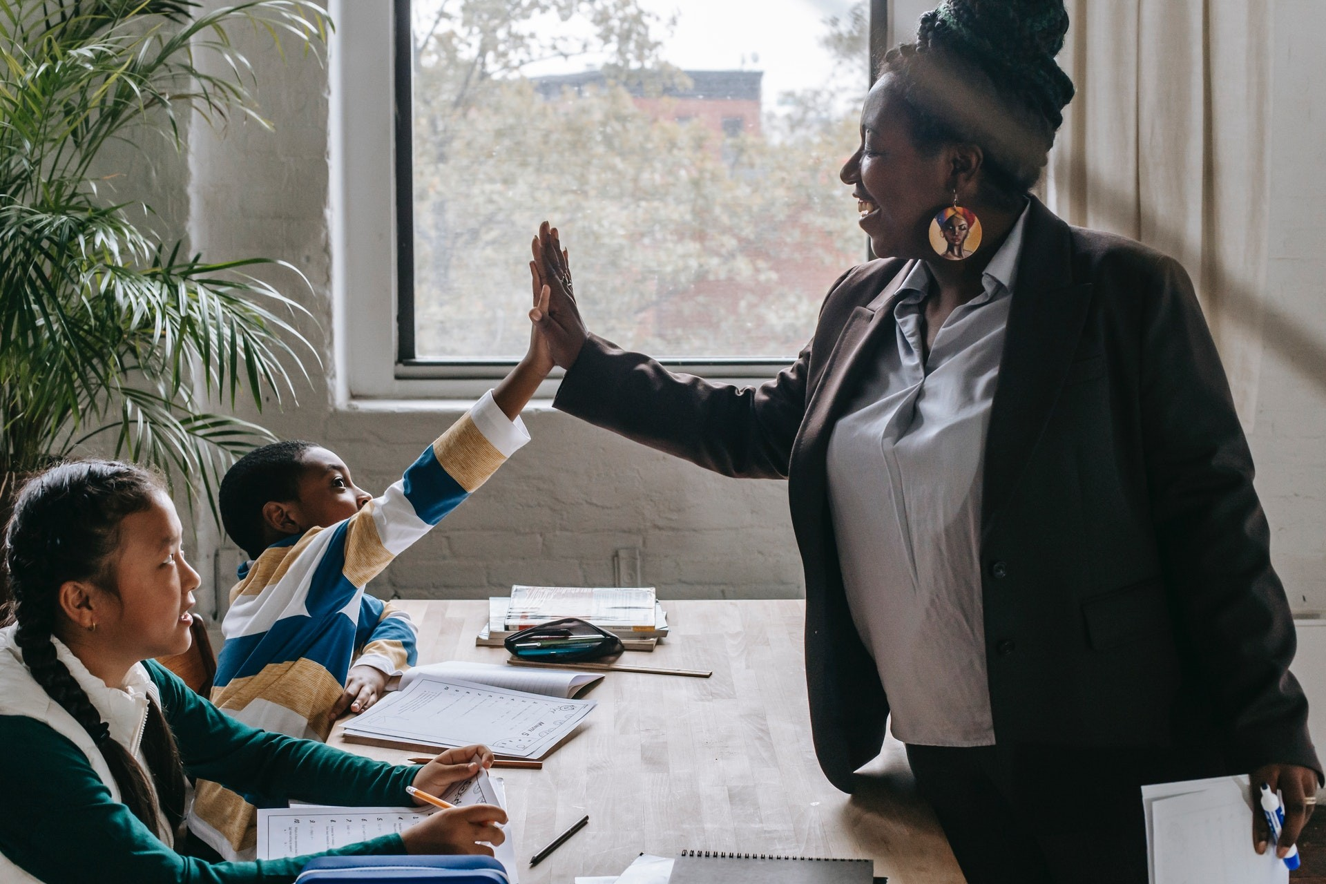 A teacher high-fives a student in her classroom as she teaches elementary math.