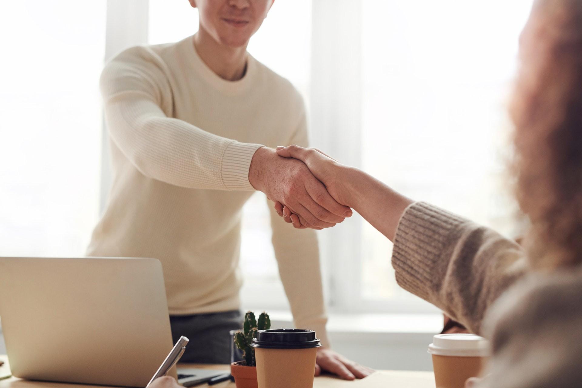 A teacher and a parent shake hands across a desk.