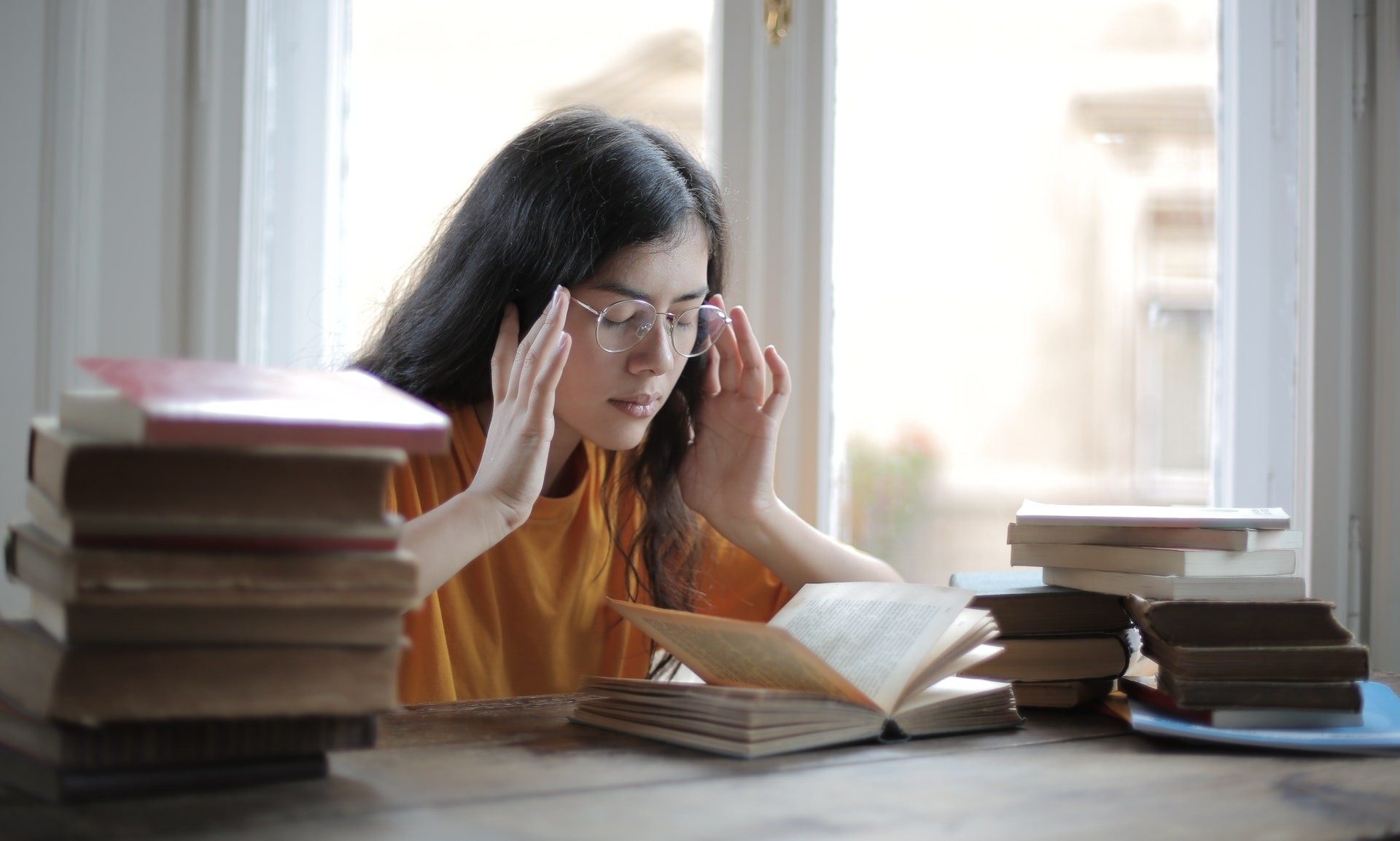 A high school student sits next to several piles of books and touches her temples as she struggles with rote memorization.