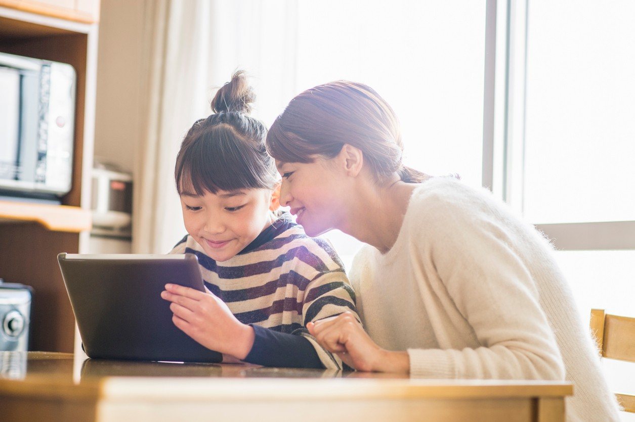 A mother sitting with child learning on a tablet
