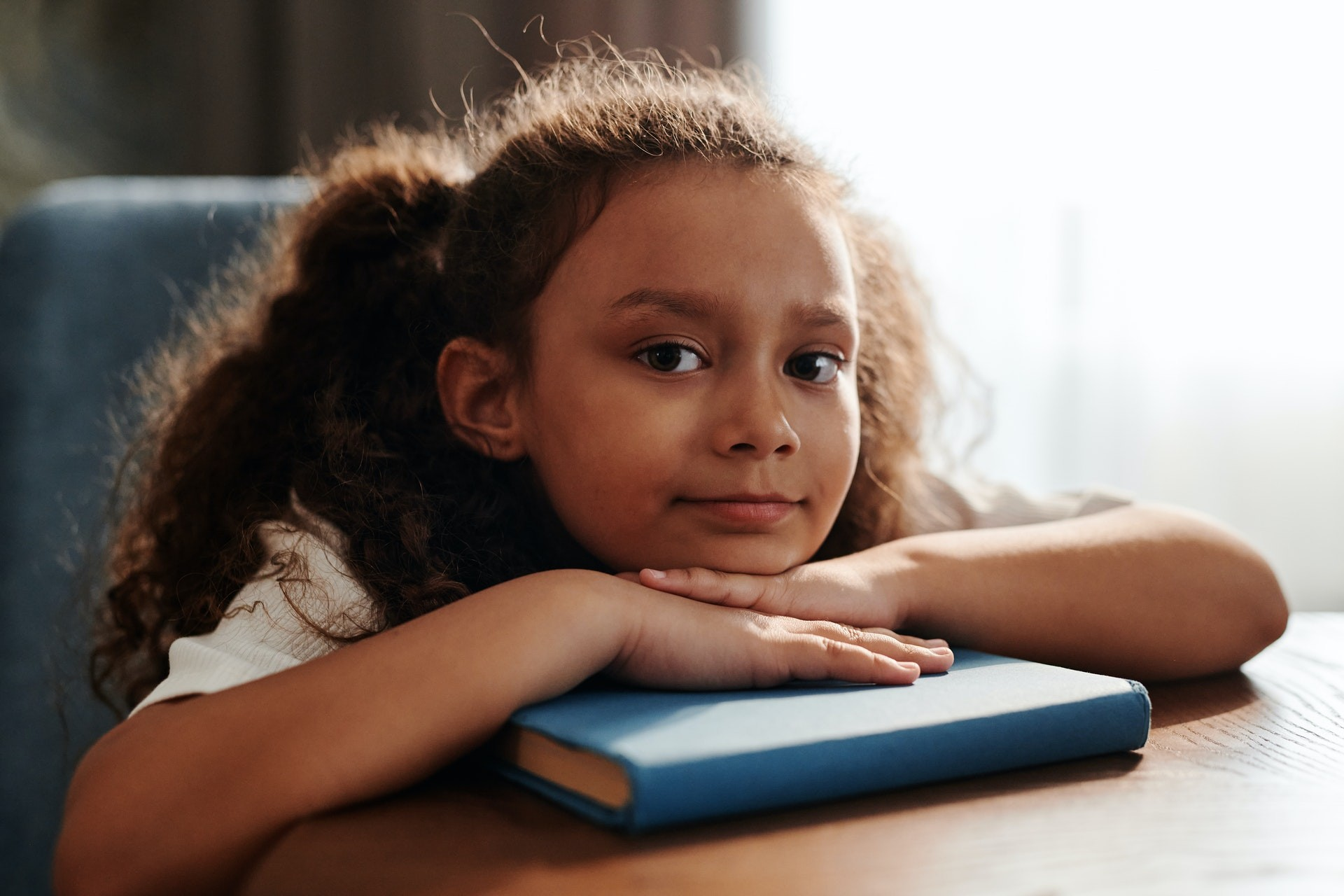 Young girl rests her head on a book and looks into the camera.