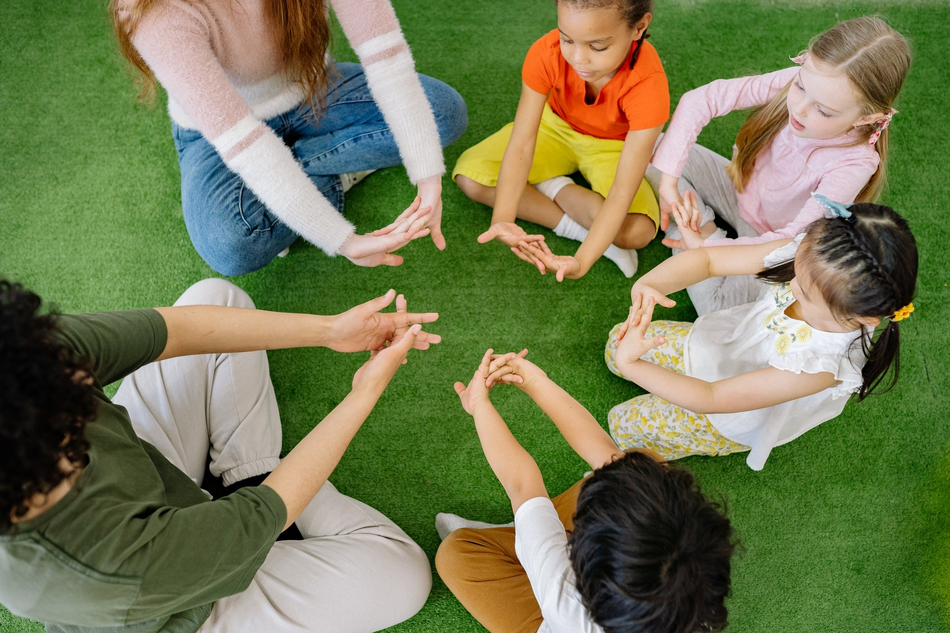 Four young students and two teachers sit in a circle and stretch their hands.