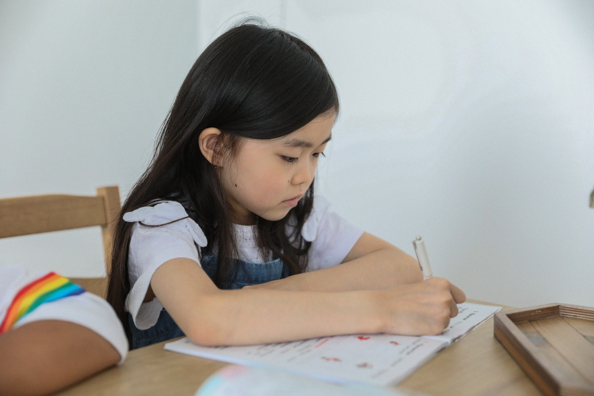 A young student works on her math homework in the classroom