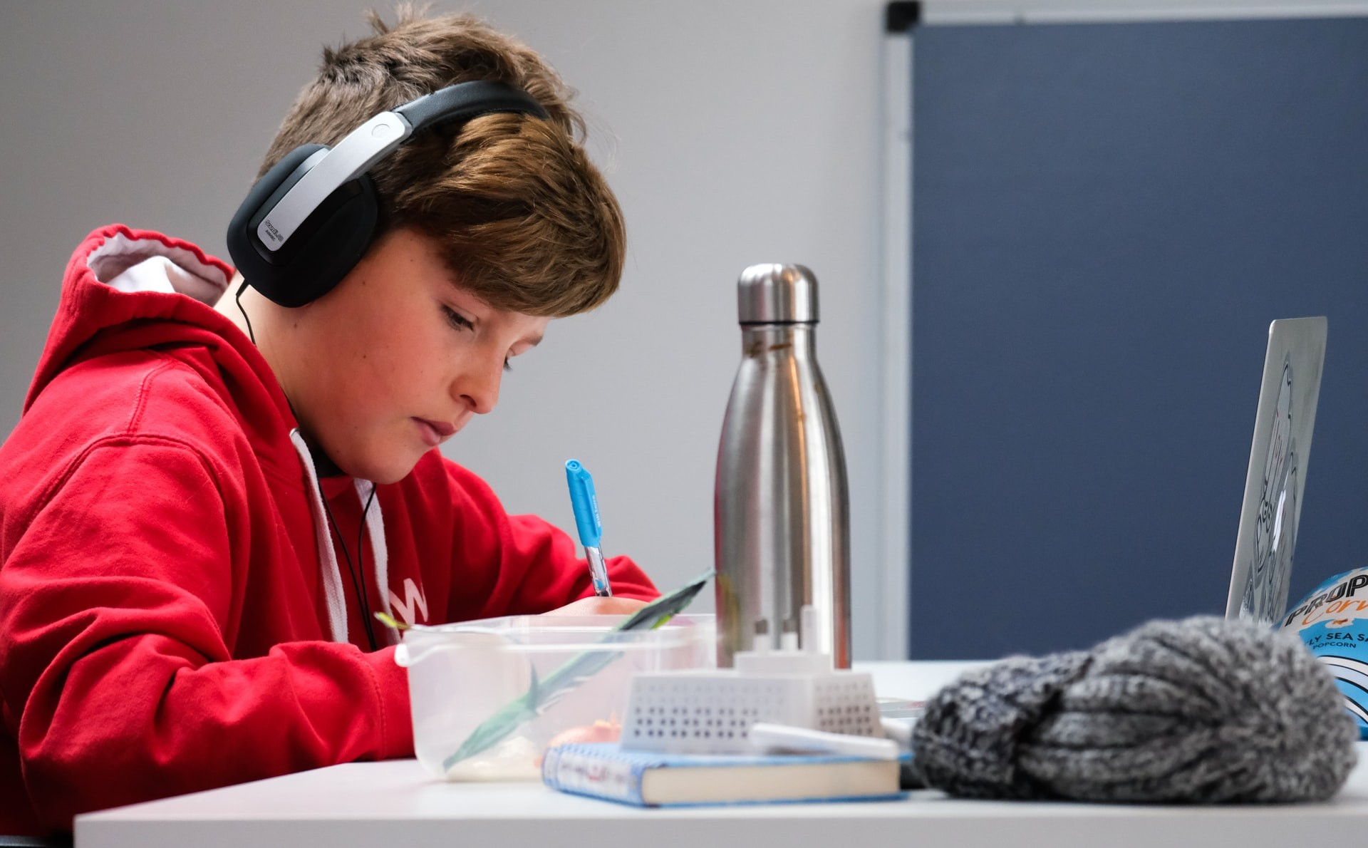 A young boy wears headphones and uses aural study strategies to prepare for his test.