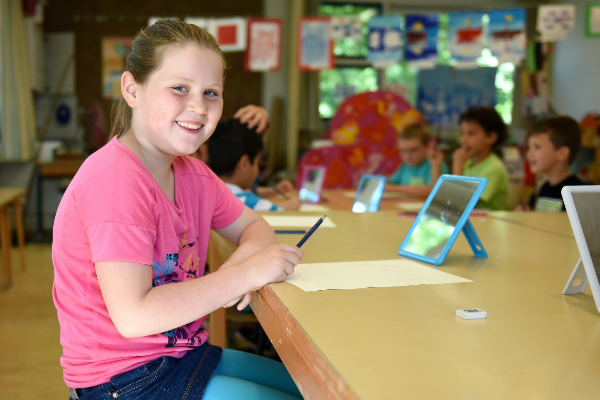 Young elementary student play on a tablet during math class
