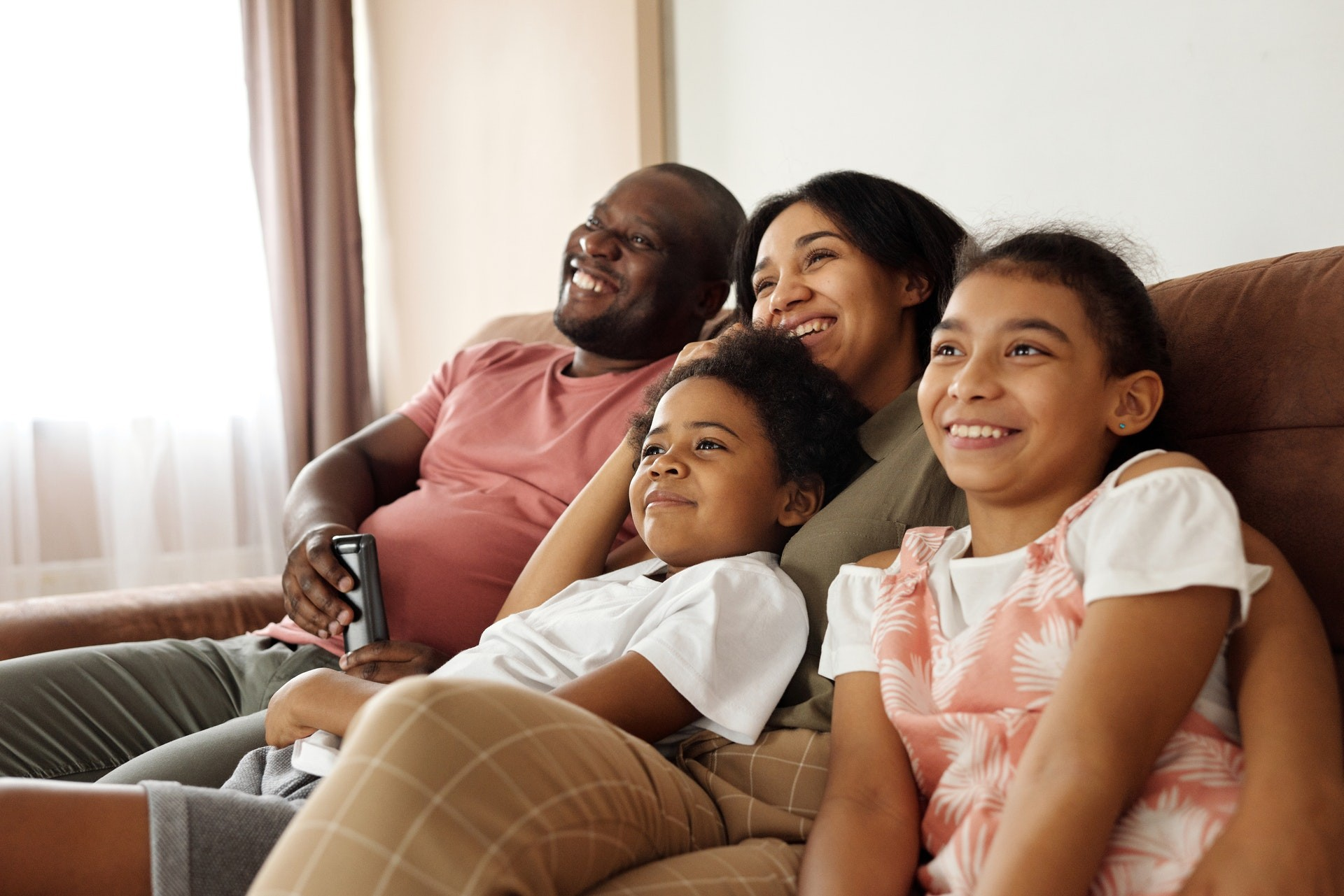 A family of four sits on a couch and smiles at a TV offscreen while they do earth day activities.