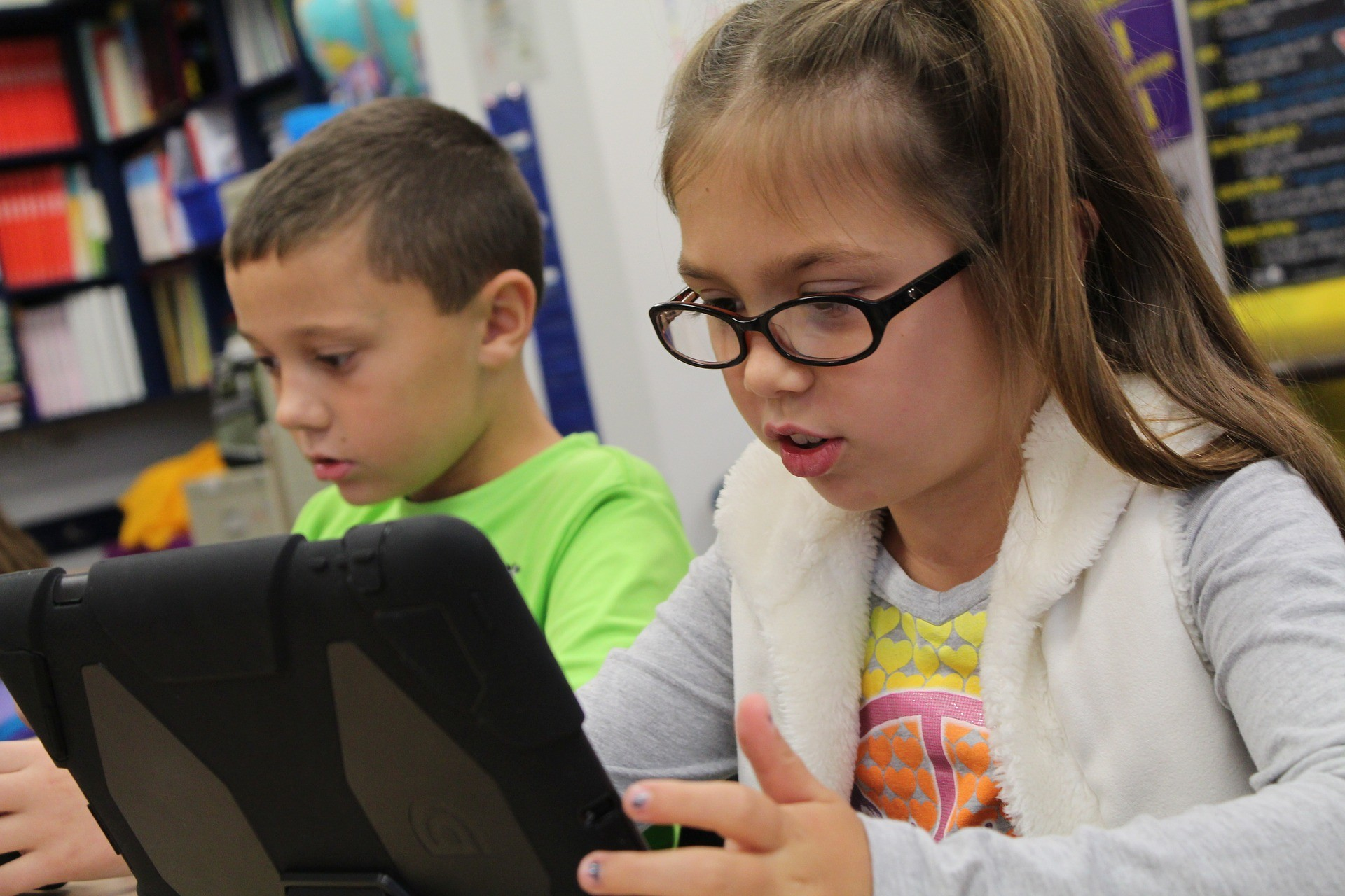 Two children work on tablets in a classroom.