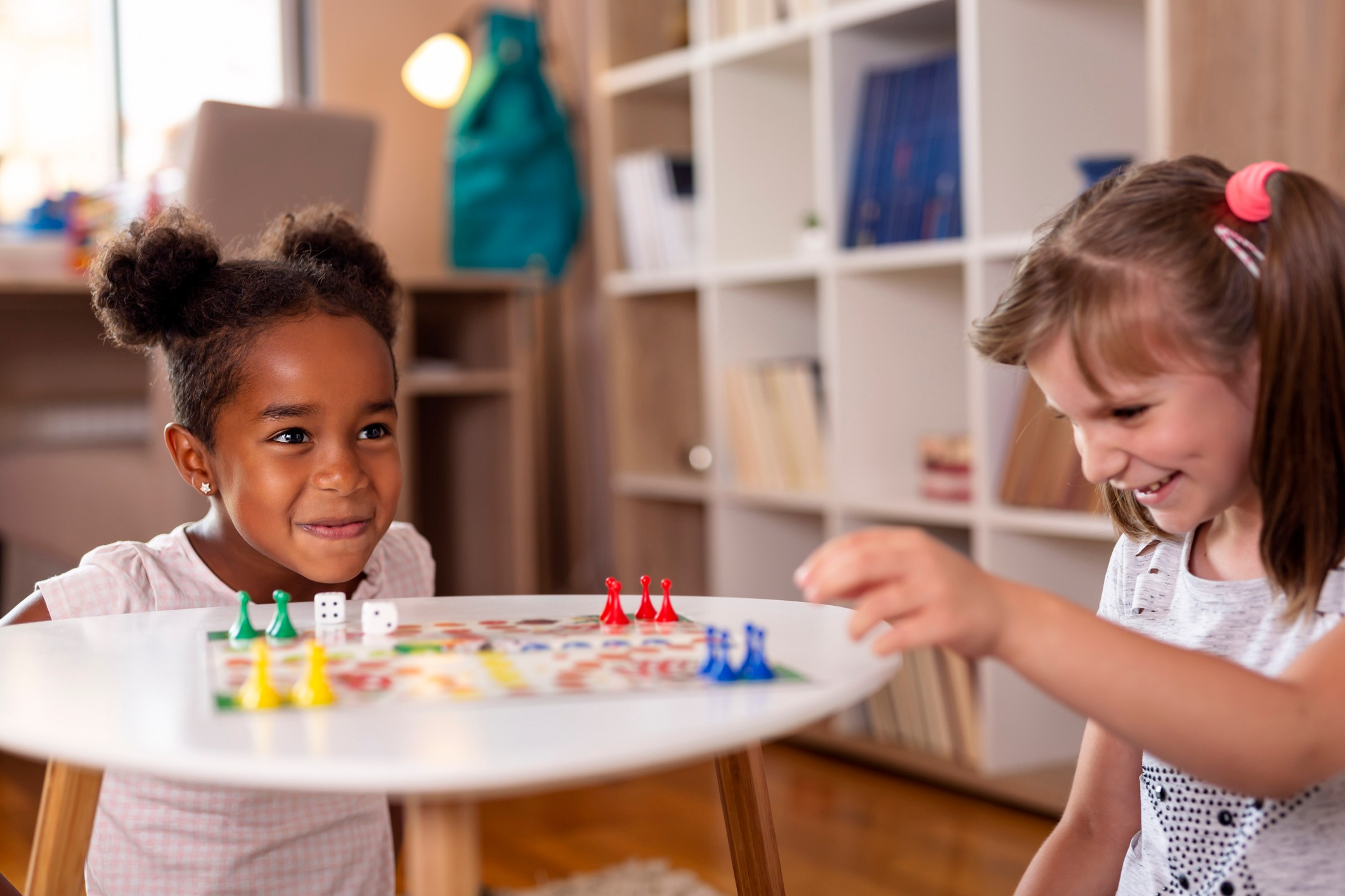 Two young girls playing a board game at home.