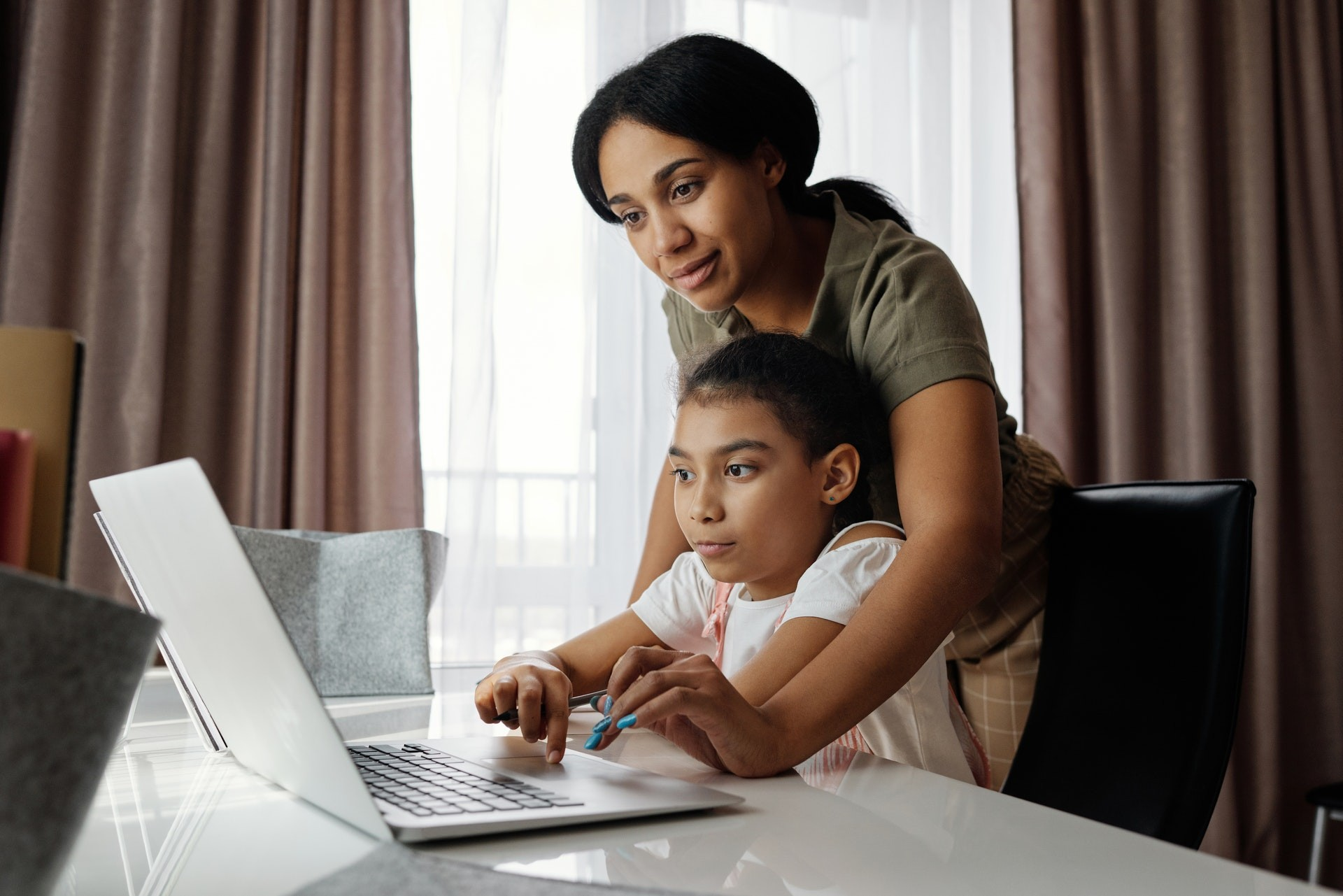 Mother and daughter work together on a computer