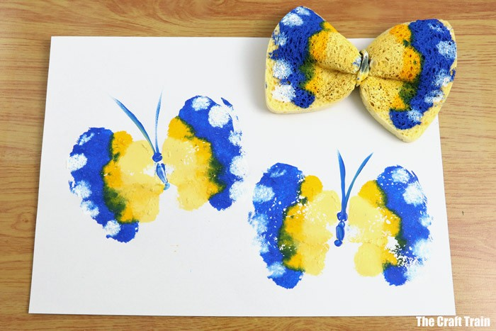 Blue and yellow butterfly painting with paint-covered kitchen sponge above it.