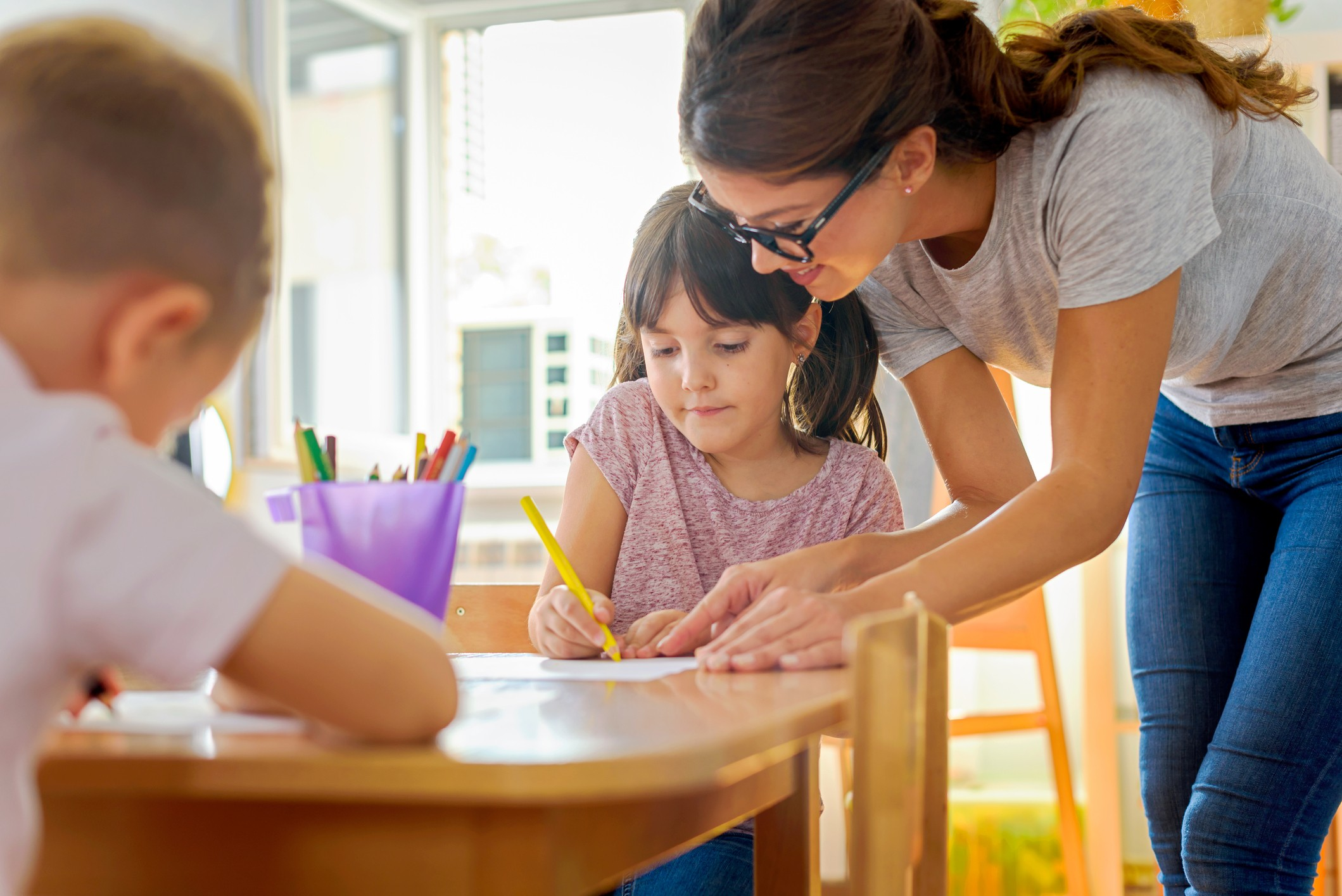 A teacher works one on one with a kindergarten student working at a wooden table.