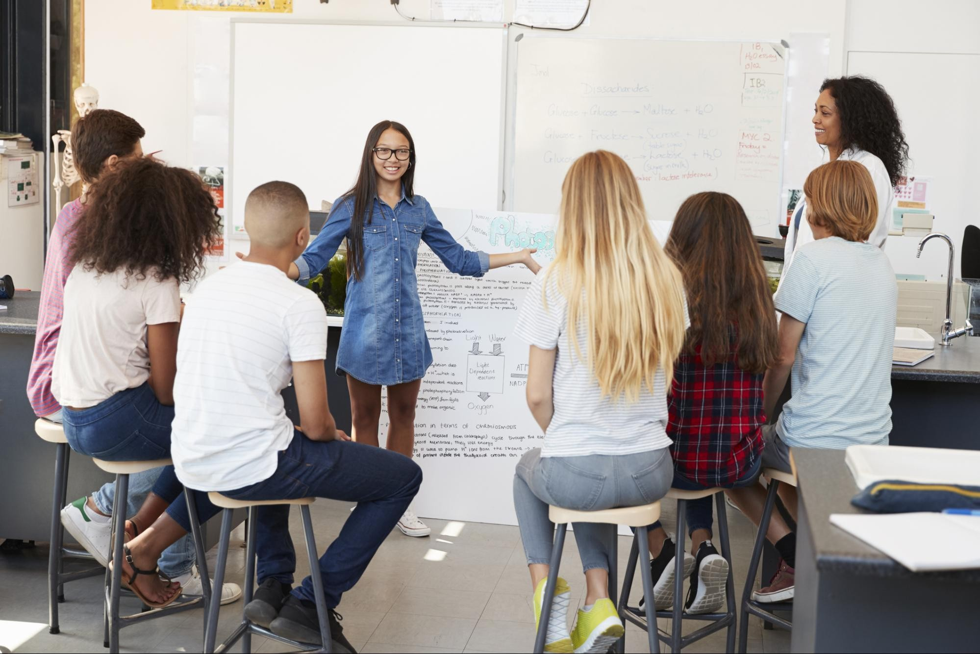 A high school student stands in front of her classmates and presents a project.