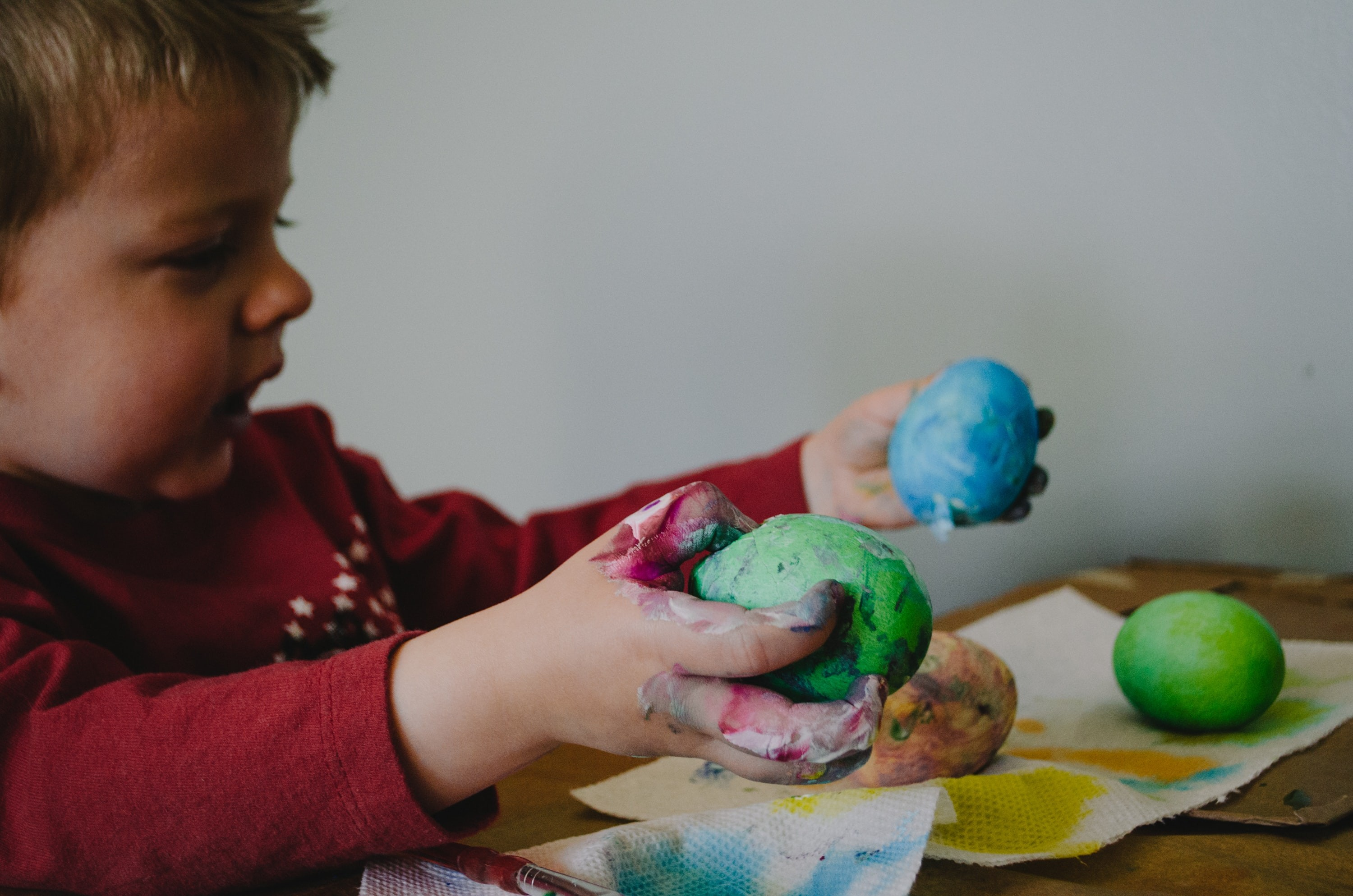 A child plays with colorful salt dough while doing earth day activities for kids.