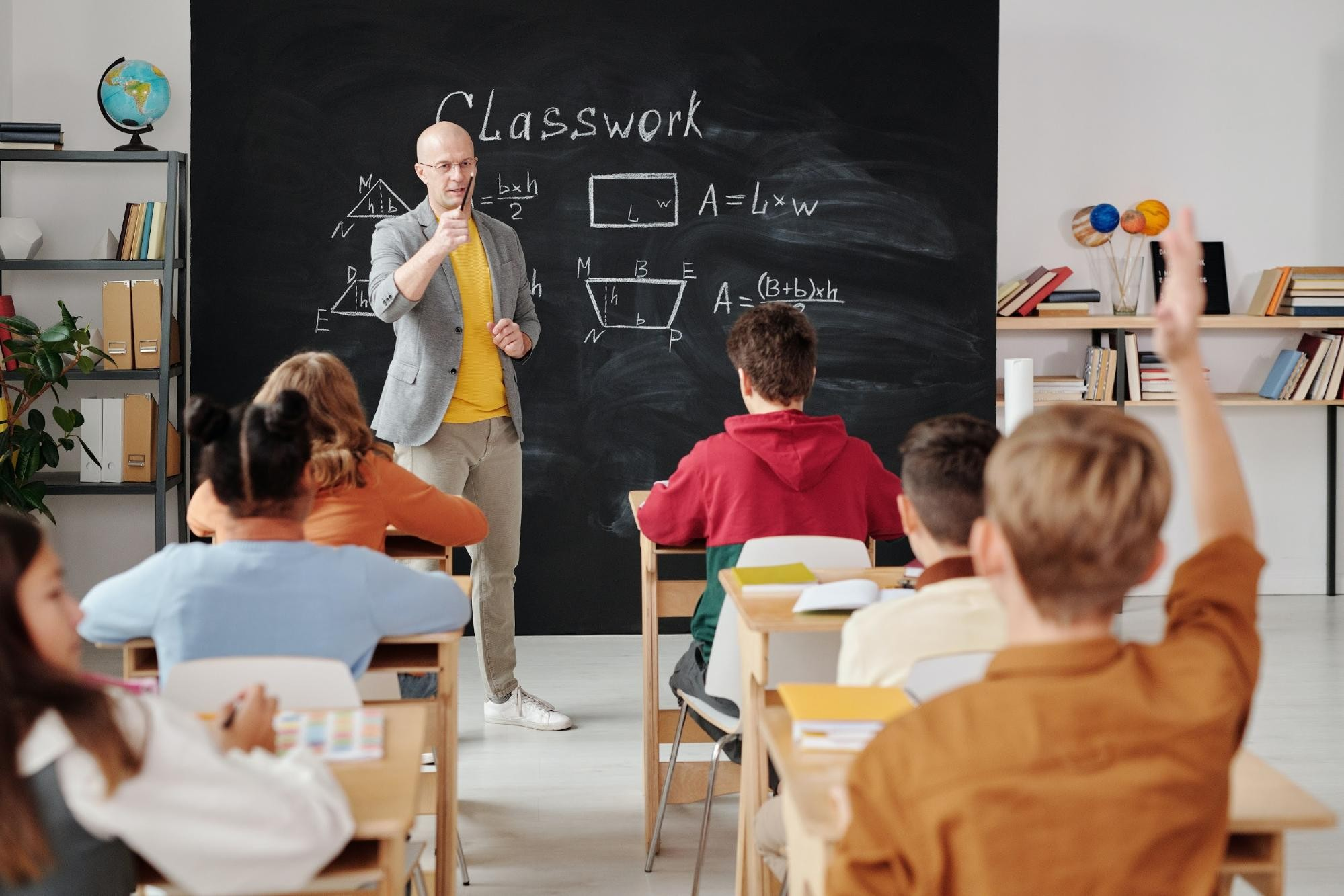 Teacher standing in a classroom in front of a blackboard, pointing at a student who is raising their hand.