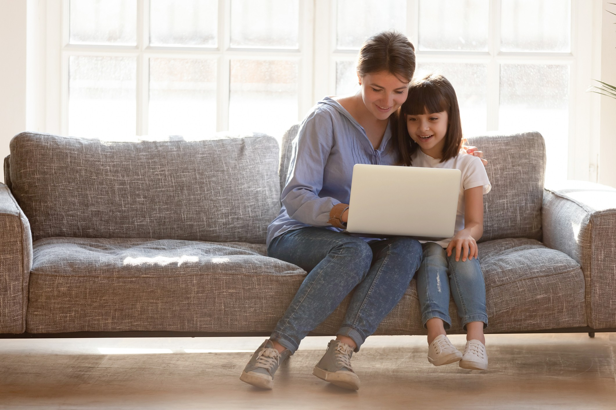 Parent and child sitting on the couch on a laptop together