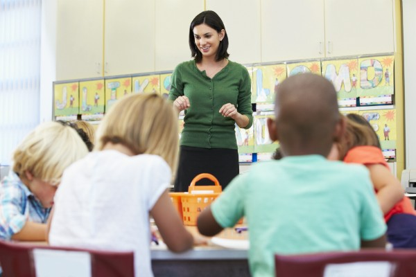 A teacher stands at the front of the classroom, using hand motions to supplement her talking.