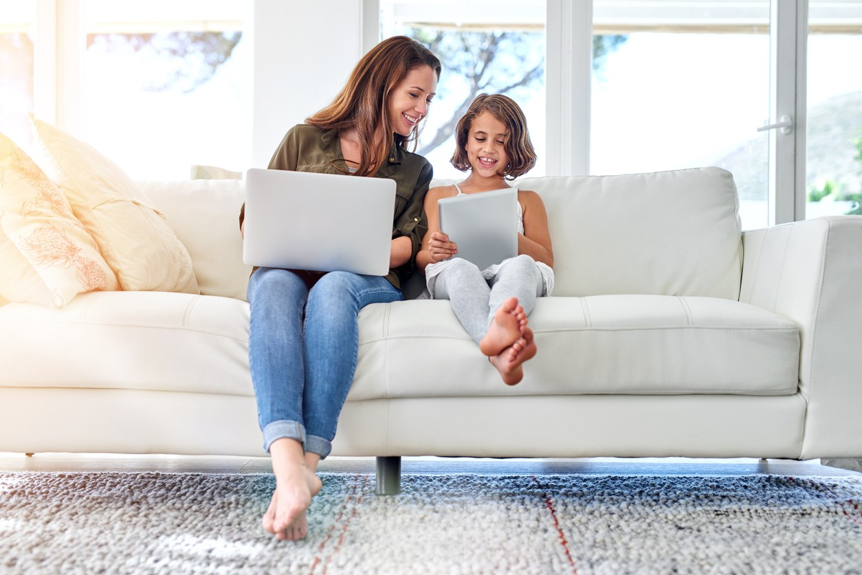 mother and daughter sitting on a couch together on their laptops