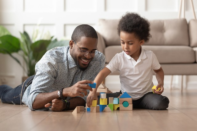 Father and son building a house out of blocks together