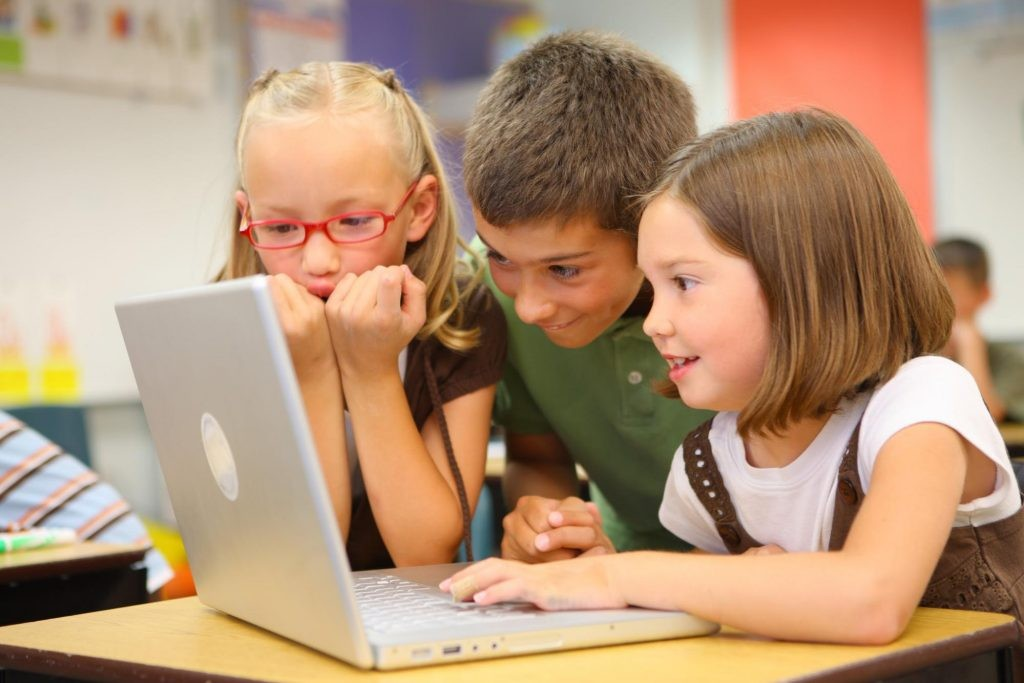 three students are looking at their laptop
